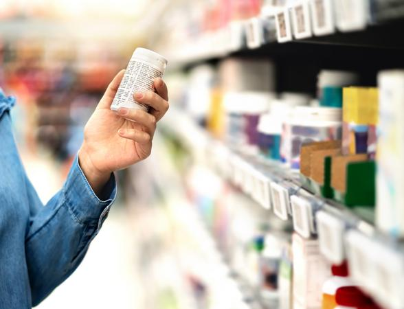 Person picking medicine bottle from pharmacy shelf