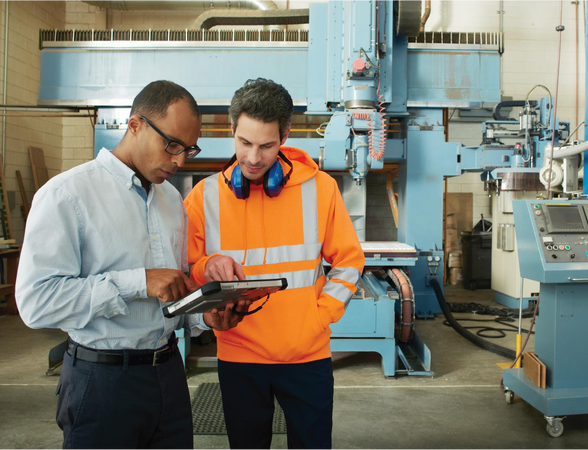 Mid aged manager and young factory worker looking at tablet