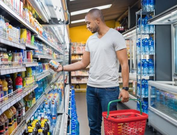 Mid aged man in departmental store aisle picking goods from shelf